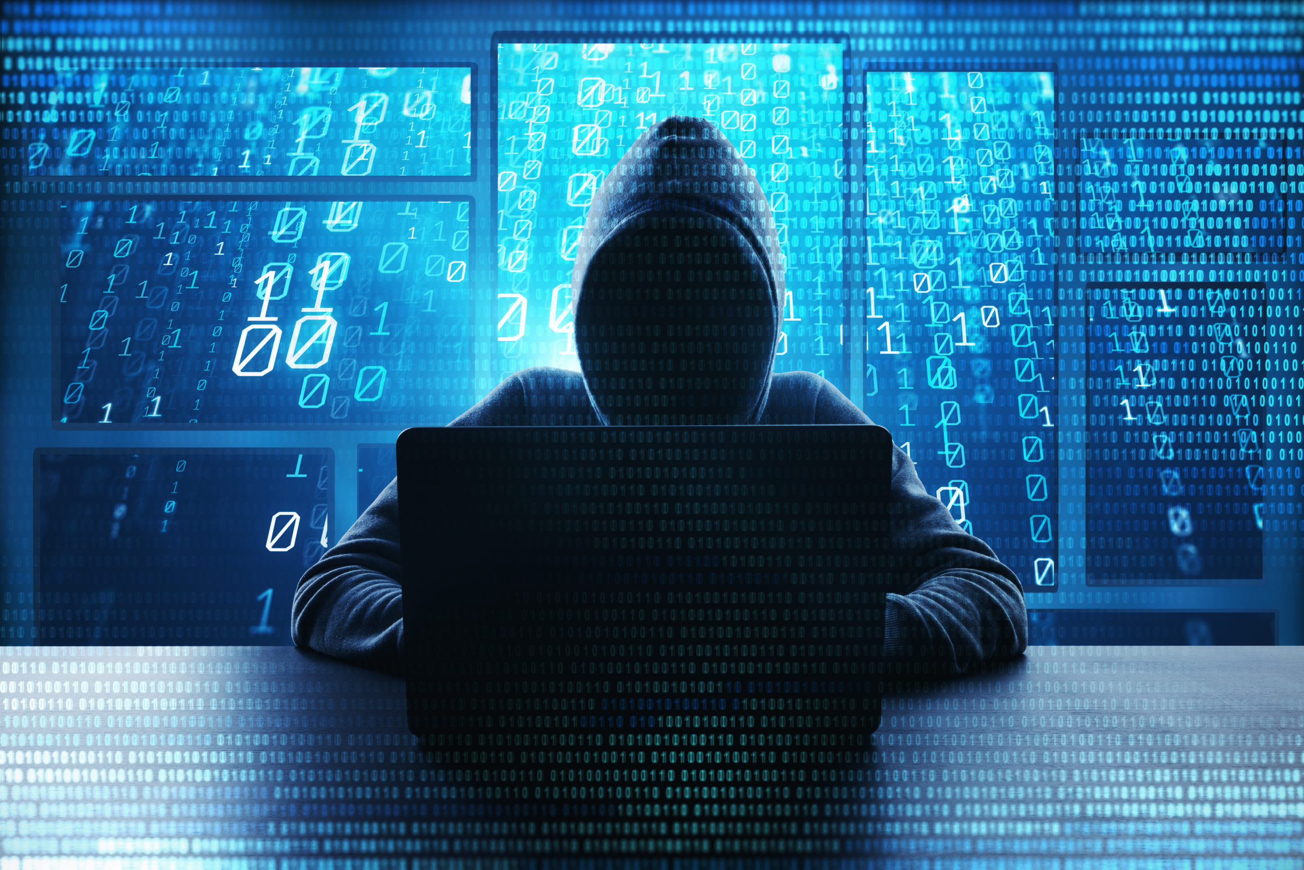 Hacking and malware concept. Hacker using abstract laptop with binary code digital interface.