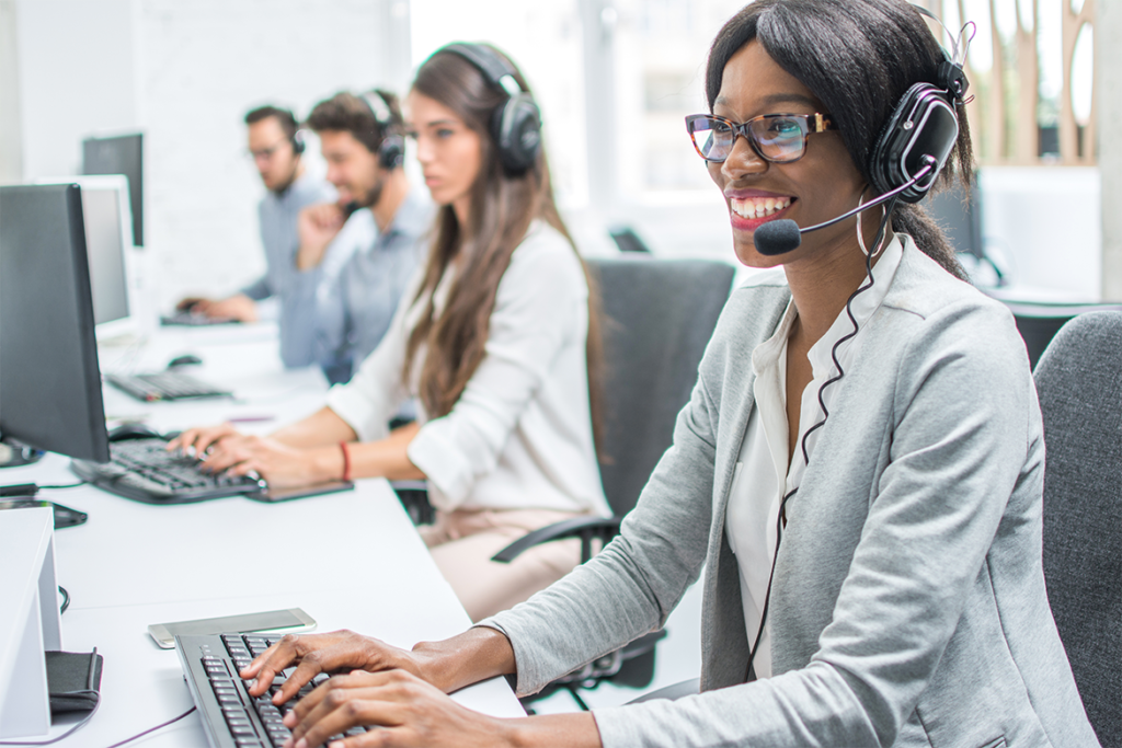 Smiling IT support technician with headset working in call center